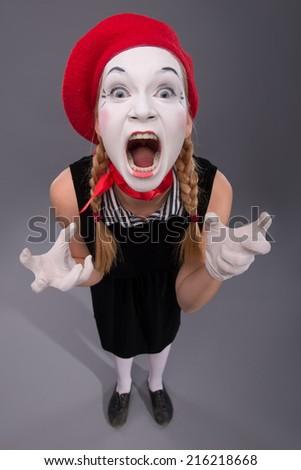 Top-view portrait of funny female mime in red head and with white face very loudly shouting at looking at the camera isolated on grey background with copy place - stock photo