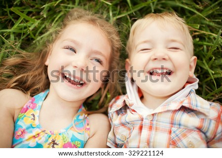 Top view portrait of two happy smiling kids lying on green grass. Cheerful brother and sister laughing together. - stock photo
