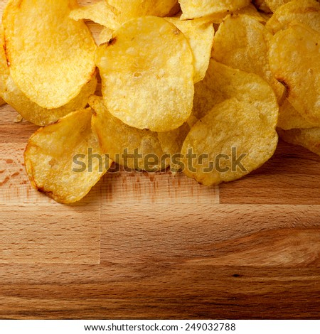 Top view potato chips over wooden table - stock photo