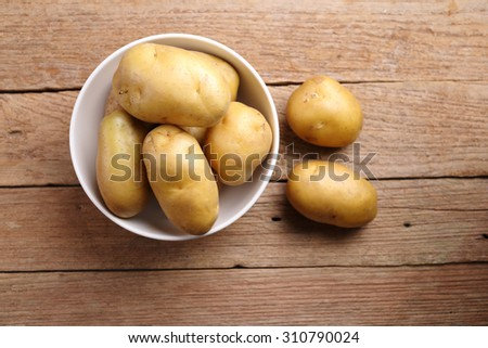 Top view Potatoes in bowl with wooden background - stock photo