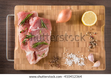 Top view raw pork chop steak and garlic, pepper, onion on wooden bamboo background with free text space. - stock photo