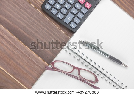 Top view red heart, calculator, pen, glasses and  planner on wooden background