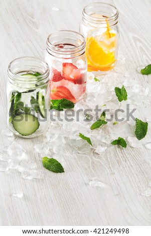 top view row rustic jars in crashed ice cubes with orange,strawberry,cucumber and mint prepared to make fresh homemade lemonade with sparkling water Cool down beverage in summer - stock photo
