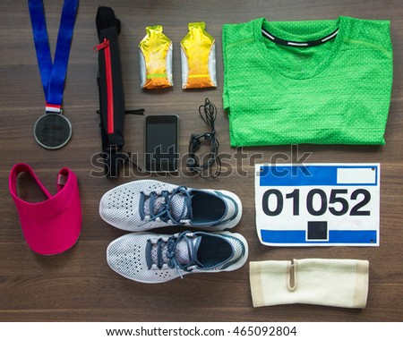 Top View Running Shoes, Marathon Race Bib (number), Medal, Runners Gear And Energy Gels On Wood Background, Sport, Fitness And Healthy Lifestyle Concept.