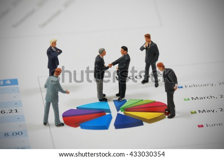 Top view selective focus of miniature businessman handshake on colorful circle chart background as partnership and investment concept. - stock photo