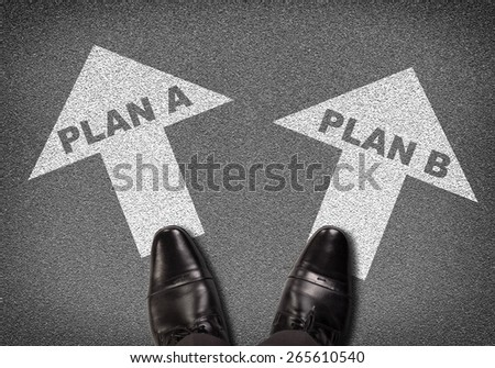 Top view. Shoes standing on asphalt road with two arrows. Labels plan A and plan B. Business concept - stock photo