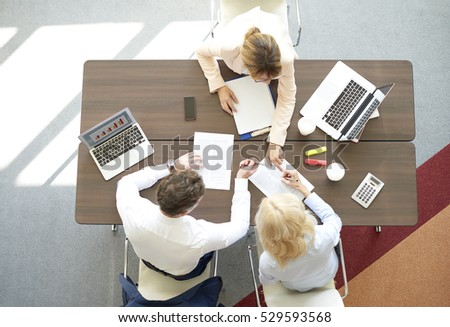 Top view shot of a business team working on new financial investment. Group of coworkers doing some paperwork while sitting desk surrounded computers.