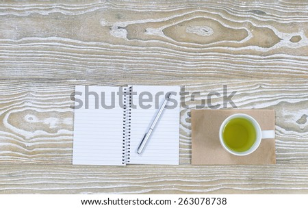 Top view shot of an old white desktop with notepad, pen and green tea in cup in horizontal format with plenty of copy space.  - stock photo
