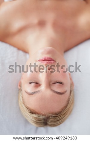 Top view shot of beautiful young caucasian woman lying with her eyes closed on a massage table at dayspa - stock photo