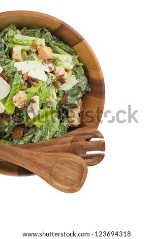 Top view shot of caesar salad on a wooden bowl with wooden ladle and fork placed at the side - stock photo