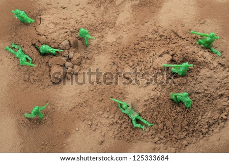 Top view shot of fighting toy soldiers in brown soil - stock photo