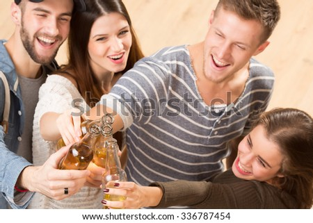 Top view shot of happy friends with alcohol cocktails making cheers. Two men and two women spending their free time in good company.