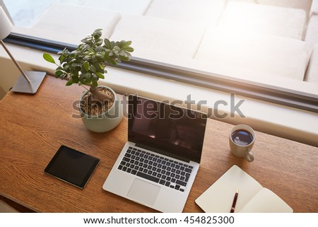 Top view shot of laptop computer, digital tablet, potted plant, diary and a cup of coffee on wooden table. Modern work desk by a window. - stock photo