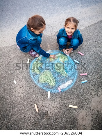 Top view shot of two girls drawing Earth with chalks - stock photo