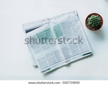 Top view stack newspaper and cactus pot on workplace white desk of office