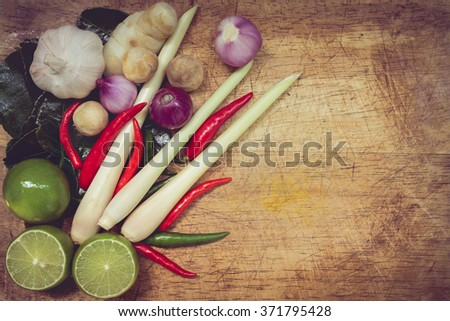 Top view. Still life kaffir lime leaf, lemon, lemongrass, galangal, chili, onions and Straw mushroom herb and spicy ingredients Thai food over chopping block on wood background. Low key picture style. - stock photo