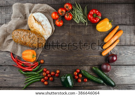 Top view studio shot of fresh vegetables on wooden table. Empty space for logo on center. There are onion, apple, pepper, hot pepper, cucumber, tomato, carrot, green peas and bread