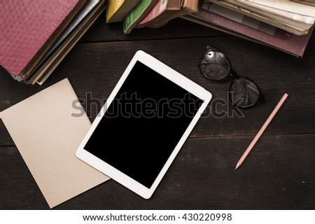 Top view tablet pc and old book on reading wood table  - stock photo
