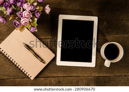 Top view Tablet PC coffee and notebook on wooden table