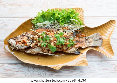 Top view, Thai style food main course: whole fried sea bass with garlic  - stock photo