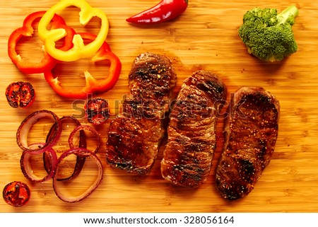 Top view, There are  three juicy steak medium rare, near fresh vegetables for garnish on the light wooden table. Serving meat with vegetables for dinner - stock photo