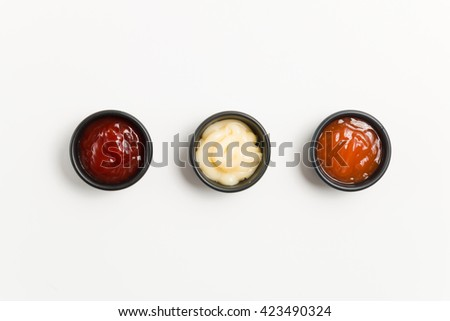 top view three sauce ketchup mayonnaise and chilli sauce in black bowl isolate on white background