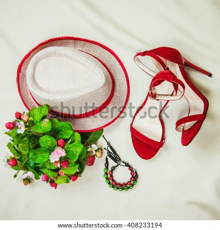 Top view to a composition of summer female fashion items with red color base: high heels sandals, a hat, bracelet and strawberry flowers and berries. Light color background. - stock photo