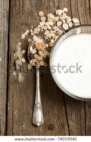 Top view to bowl of yoghurt with muesli and silver spoon on old wooden desk - stock photo