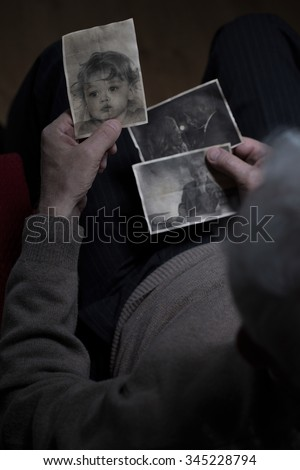 Top view to elder man watching his family pictures - stock photo