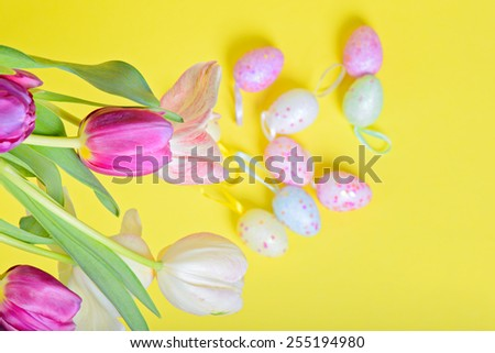 Top view to the easter multicolored tulips and eggs over yellow paper - stock photo