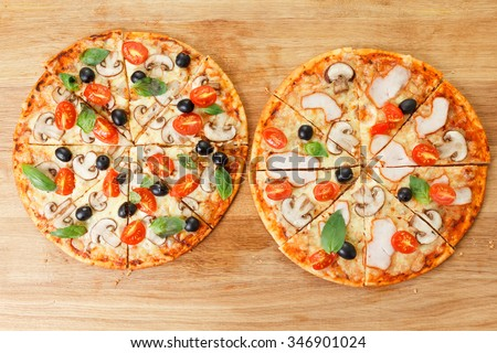 Top view two Pizza with mushrooms, olives and tomatoes. Basil, rosemary and fresh vegetables. Freshly homemade  - stock photo