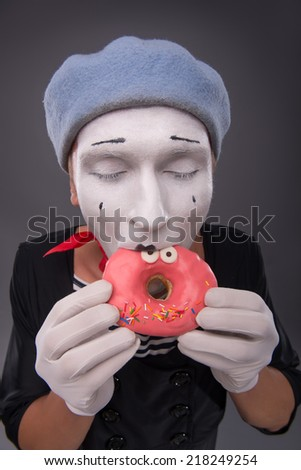 Top-view waist-up portrait of handsome male mime holding with both hands and delighting with closed eyes  a tasty pink donut with funny eyes on it, isolated on grey background with copy place