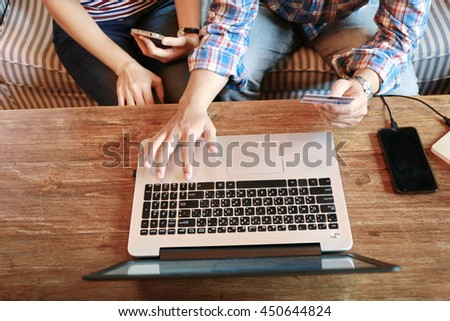 top view women working laptop and man hand use phone on wood table,the internet of things.Two young business people touching on mobile phones while working and discussion and brainstorming  in office. - stock photo