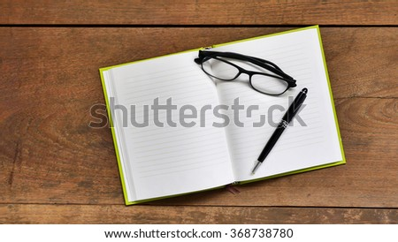 Top view workspace with blank notebook ,glasses and pen on wooden table background . - stock photo