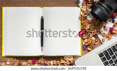 Top view workspace with blank notebook,laptop,camera and dried flowers on wooden table background . - stock photo