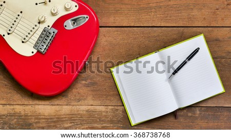 Top view workspace with blank notebook,pen and Electric guitar on wooden table background . - stock photo
