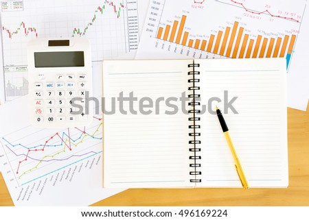 Top view workspace with booklet, pen and graphs. Wooden table background in vintage toned.