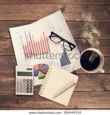 Top view workspace with booklet, pen, glasses, cup of coffee and graphs. Wooden table background in vintage toned. - stock photo