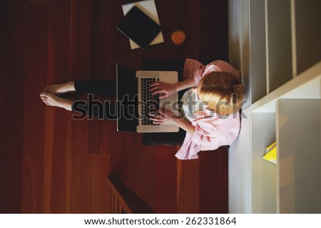 Top view young female freelancer busy working on laptop computer while leaning on home bookshelf sitting on the floor, charming business woman working from home while having breakfast, young student - stock photo
