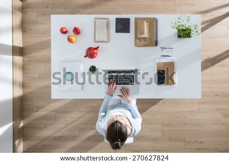 top view, young woman sitting at desk and working on her laptop, her table is perfectly tidy, the sun casts graphics shadows on the wood floor - stock photo