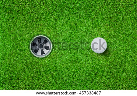 Top views of golf ball and golf hole on green grass texture background.