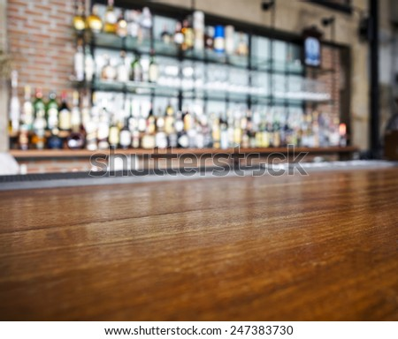 Top wooden table with Bar Blurred Background - stock photo