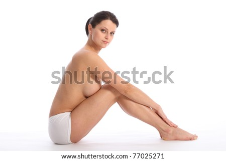 Topless beautiful healthy young woman wearing white sports knickers, sitting on floor with knees raised against white background showing off a sexy fit body. - stock photo