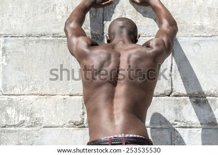 Topless, fit muscular african american male model isolated against a white concrete wall, wearing maroon shorts. - stock photo