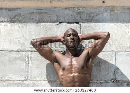 Topless, fit muscular african american male model isolated against a white concrete wall, wearing maroon shorts.