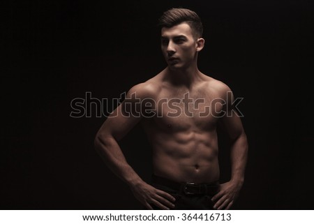 topless fit young man posing in dark studio background with hands on waist while looking away