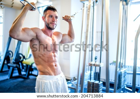 Topless man, bodybuilder and muscular man working the biceps at gym, showing abs - stock photo