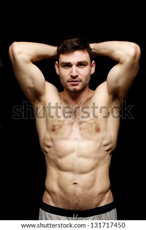 Topless man stood with his hands behind his head isolated on a black background