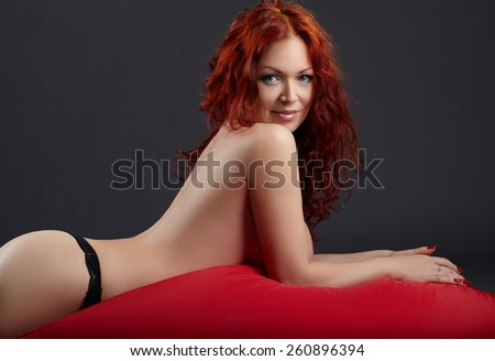 Topless redhead woman posing lying in studio - stock photo