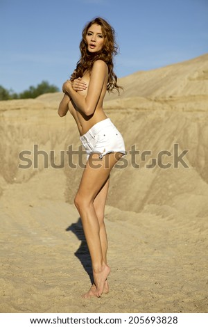 topless sensuality brunette girl in white  jeans over sand background - stock photo